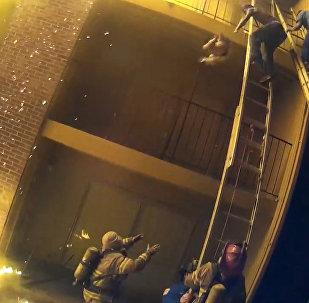 Спасатель поймал девочку, сброшенную с 3-го этажа во время пожара