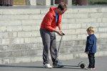 Папа учит сына кататься на самокате