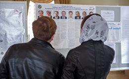 Избиратели последний раз изучают кандидатов в президенты России 2018 на избирательном участке No8031, Гюмри