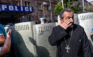 Священник перед отделением полиции, где предположительно находится Никол Пашинян (22 апреля 2018). Ереван