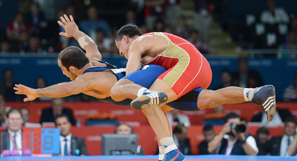 Борцы Роман Власов (Россия) и Арсен Джулфалакян (Армения) (справа налево) в финальном поединке на соревнованиях по греко-римской борьбе в весовой категории до 74 кг на XXX летних Олимпийских играх в Лондоне.