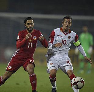 Артур Саркисов ведет борьбу за мяч с капитаном сборной Черногории Стеваном Джоветичем