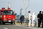 Пожарные и спасатели наблюдают за уровнем воды с моста в Сома после предупреждения о цунами в Японии