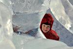 Малыш возле снежно-ледовых скульптур