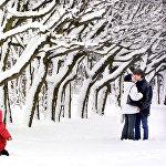 Малыш радуется снегу, пока мама с папой целуются в парке