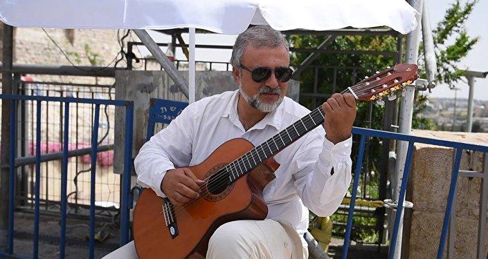 Музыкант группы Романтик Трио играет Ов сирун, сирун возле старого города Иерусалима