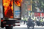 Сотрудники сил безопасности собираются рядом с правительственным грузовиком, который был подожжен во время митинга против правительства президента Венесуэлы Николаса Мадуро в Каракасе, Венесуэла