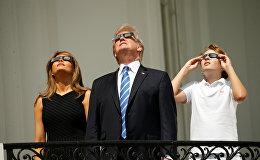 Президент США Дональд Трамп, Первая леди США Меланья Трамп и их сын Бэррон Трамп наблюдают полное солнечное затмение в США