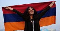 Участница XIX Всемирного фестиваля молодежи и студентов с флагом Армении во время шоу Россия в Сочи.